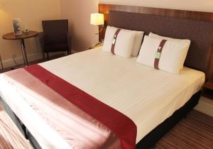 A bed or beds in a room at Holiday Inn Rotherham-Sheffield M1,Jct.33