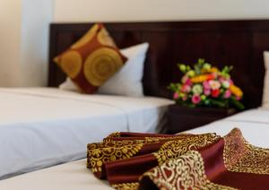 A bed or beds in a room at Azura Hotel