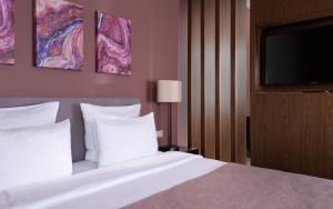 A bed or beds in a room at Green Flow Hotel Rosa Khutor