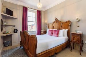 A bed or beds in a room at Jolyon's Boutique Hotel