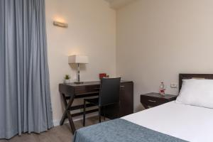 A bed or beds in a room at Sharon Hotel Herzliya