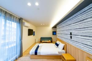 A bed or beds in a room at GRAND BASE Hiroshima Hikarimachi