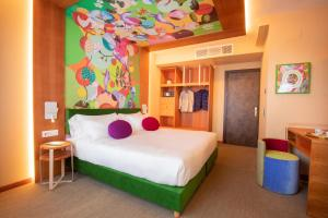 A bed or beds in a room at OMAMA Hotel