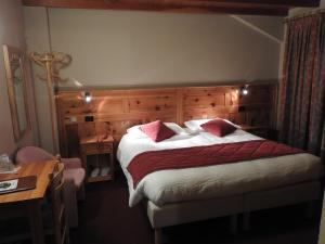 A bed or beds in a room at Hotel Le Clocher