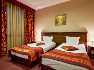 A bed or beds in a room at Yantra Grand Hotel