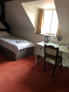 A bed or beds in a room at Tudor House Hotel