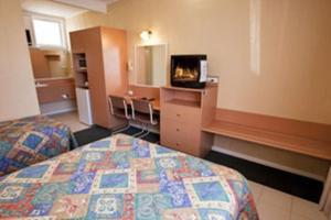 A bed or beds in a room at Parkville Motel