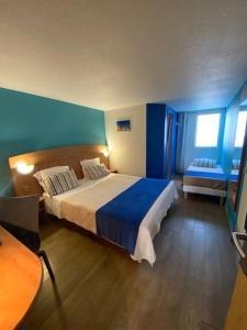 Ein Bett oder Betten in einem Zimmer der Unterkunft Hôtel De La Plage