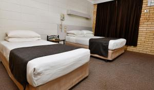 A bed or beds in a room at Burke and Wills Motor Inn