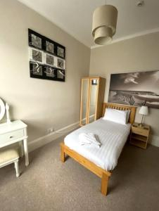 A bed or beds in a room at Somerton Lodge Hotel