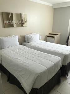 A bed or beds in a room at Samba Macaé