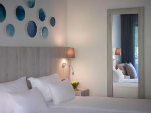 A bed or beds in a room at Rhodes Bay Hotel & Spa