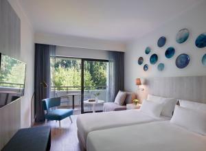 מיטה או מיטות בחדר ב-Rhodes Bay Hotel & Spa