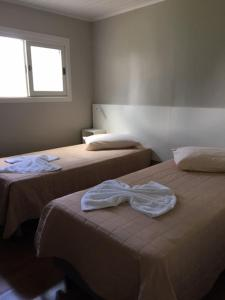 A bed or beds in a room at Pousada dos Pinheirais