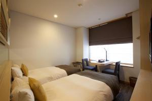 Un ou plusieurs lits dans un hébergement de l'établissement Miyajima Grand Hotel Arimoto