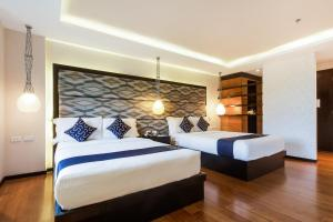 A bed or beds in a room at Capital O 261 Rumah Highlands Hotel