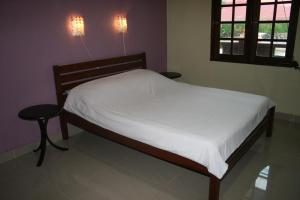 A bed or beds in a room at Balai Serama Guesthouse