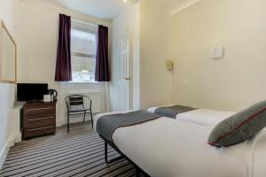 A bed or beds in a room at Enrico Hotel