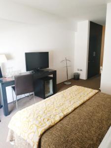 Una televisión o centro de entretenimiento en Hotel Alborada