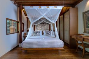 A bed or beds in a room at Tandjung Sari Hotel