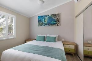A bed or beds in a room at BIG4 Adventure Whitsunday Resort