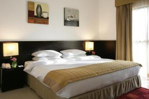 A bed or beds in a room at Ramada Hotel & Suites by Wyndham Ajman