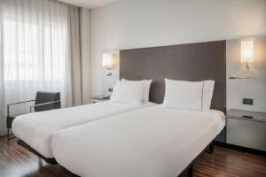 A bed or beds in a room at AC Hotel by Marriott Pisa