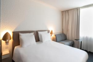 A bed or beds in a room at Novotel Evry Courcouronnes