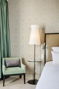 A bed or beds in a room at Le Grand Hotel Cabourg - MGallery