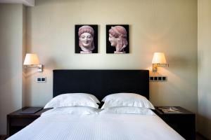 A bed or beds in a room at The Athens Gate Hotel