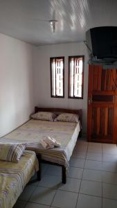 A bed or beds in a room at Pousada Fundo de Quintal