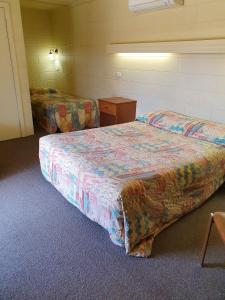 A bed or beds in a room at Opal Inn Hotel, Motel, Caravan Park