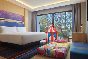 A bed or beds in a room at Aloft Langkawi Pantai Tengah