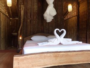 เตียงในห้องที่ The Tropical Koh Mook