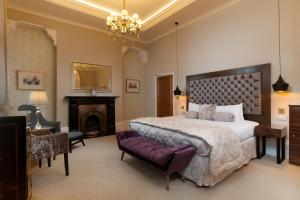 A bed or beds in a room at Lansbury Heritage Hotel