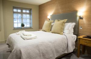 A bed or beds in a room at The Legh Arms Prestbury