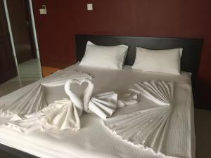 A bed or beds in a room at Nallur Residence