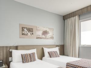 Cama ou camas em um quarto em OYO CHA Pampulha Design Hotel