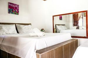 A bed or beds in a room at Cururupe Praia Hotel