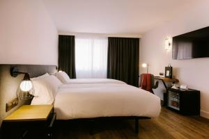 A bed or beds in a room at Centric Atiram Hotel
