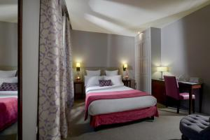 A bed or beds in a room at Hôtel Le Relais Saint Charles