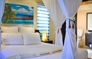A bed or beds in a room at Taveuni Palms Resort