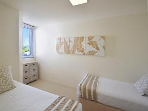 A bed or beds in a room at Fairshore Noosa