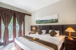A bed or beds in a room at Legian Village Beach Resort
