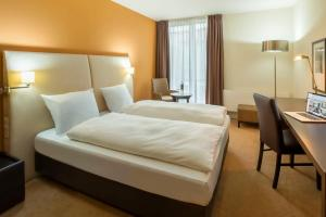 A bed or beds in a room at The Rilano Hotel München