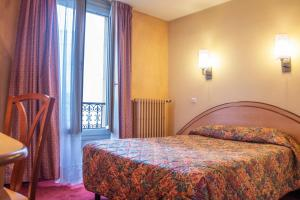 A bed or beds in a room at Hotel Terminus Montparnasse