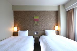 A bed or beds in a room at Daiwa Roynet Hotel Takamatsu