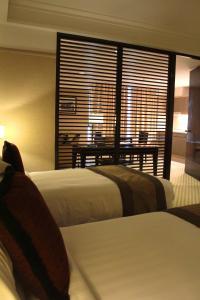 سرير أو أسرّة في غرفة في أجنحة باسيفيك ريجنسي الفندقية