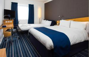 A bed or beds in a room at Holiday Inn Express Northampton - South