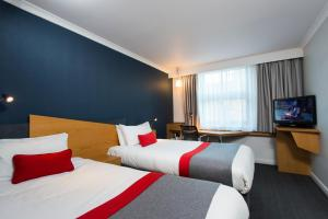 A bed or beds in a room at Holiday Inn Express Swansea East